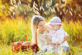Beautiful young mother and her daughter in the park — Stock Photo