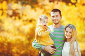 Happy family having fun outdoors in autumn in the park — Stock Photo