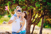 Happy young family with child resting outdoors in summer park — Stock Photo