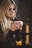 Portrait of a young woman with a cup of coffee — Stockfoto