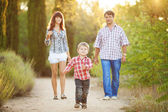 Young family walking in the summer park — Stock Photo