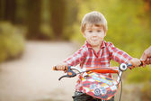 Happy boy on a bicycle in a summer park — Stock Photo