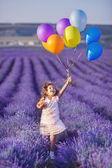 Sonriendo flores sniffing chica en un campo lila — Foto de Stock