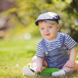 Portrait of cute little boy sitting on the grass — Stock Photo #38894069