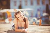 Young woman lengthened on a quay at the edge of a lake — Stock Photo