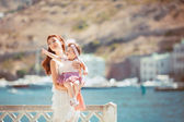 Portrait of a Happy family of woman and child having fun by the blue sea in summertime — Stock Photo