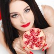 Stock Photo: Brunette girl with garnet fruit in studio