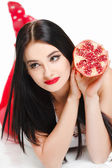 Brunette girl with garnet fruit in studio — Stock Photo