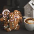 Gingerbread cookie men in a hot cup of cappuccino — Stock Photo #39625069