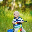 Little smiling boy on toy bicycle — Stock Photo #39671563