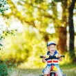 Little smiling boy on toy bicycle — Stock Photo #39671569