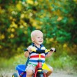 Little smiling boy on toy bicycle — Stock Photo