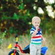 Little smiling boy on toy bicycle — Stock Photo #39671595