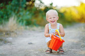 Little smiling boy with toy bucket outdoors — Stock Photo