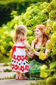 Mother and daughter playing in green summer park outdoors — Stock Photo