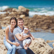 Portrait of family of three having fun together by the ocean shore and enjoying the view. Outdoors — Stock Photo