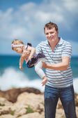 Portrait of a Happy family of man and infant child having fun by the blue sea in summertime — Stock Photo