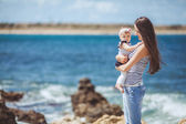 Portrait of Happy Family of two mother and child having fun by the Sea shore — Stock Photo