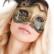 Portrait of Beautiful young blonde woman in black and gold mysterious venetian mask. Fashion photo on white background — Stock Photo #39885115