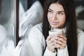 Porträtt av en ung vacker kvinna som sitter på soffan på hennes rum nära fönster i vitt — Stockfoto