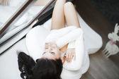 Portret van een jonge mooie vrouw zittend op de bank in haar kamer in de buurt van venster in wit — Stockfoto
