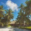 Landscape of tropical island beach with perfect sky, palms, traditional buildings — Stock Photo