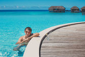 Young man in the pool and ocean in the background. Maldives — Stock Photo