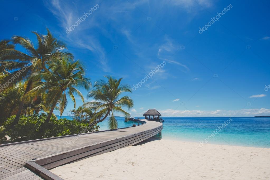 Фотообои Пейзаж тропический остров с пляжем с прекрасным небом, пальмы, традиционные здания