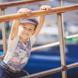 Cute little sailor boy having fan near boats on pier near the sea. Outdoor. — Stock Photo