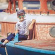 Cute little sailor boy having fan near boats on pier near the sea. Outdoor. — Stock Photo #40069413