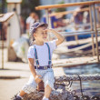 Cute little sailor boy having fan near boats on pier near the sea. Outdoor. — Stock Photo #40069529
