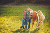 Happy family having fun with horses outdoors on green field on summer day — Stock fotografie