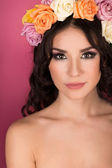 Beautiful brunette young woman with wreath of flowers studio shot pink background — Stock Photo