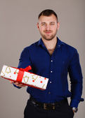 Man with muscular torso with gift box on grey background — Stock Photo