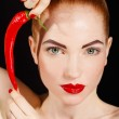 Portrait of beautiful red-haired woman with red hot spicy cayenne chili pepper — Stock Photo