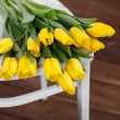 Beautiful bright yellow tulips in Still Life lying on antique white Chair — Stock Photo #40832961