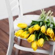 Beautiful bright yellow tulips in Still Life lying on antique white Chair — Stock Photo #40833033