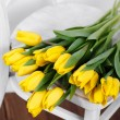 Beautiful bright yellow tulips in Still Life lying on antique white Chair — Stock Photo #40833037