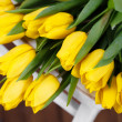 Beautiful bright yellow tulips in Still Life lying on antique white Chair — Stock Photo #40833085