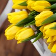 Beautiful bright yellow tulips in Still Life lying on antique white Chair — Stock Photo #40833097