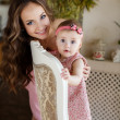 Portrait of happy young attractive mother playing with her baby girl near window in interior at haome. Pink dresses on mother and daughter — Stock Photo #40838303
