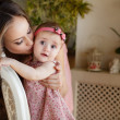 Portrait of happy young attractive mother playing with her baby girl near window in interior at haome. Pink dresses on mother and daughter — Stock Photo #40838431