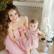 Portrait of happy young attractive mother playing with her baby girl near window in interior at haome. Pink dresses on mother and daughter — Stock Photo #40838721