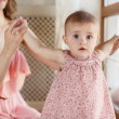 Portrait of happy young attractive mother playing with her baby girl near window in interior at haome. Pink dresses on mother and daughter — Stock Photo #40838783