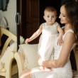 Portrait of happy young attractive mother playing with her baby girl near window in interior at haome. Pink dresses on mother and daughter — Stock Photo #40838835