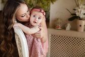 Portrét mladé atraktivní mamince hrát s její holčička okna v interiéru na haome. růžové šaty na matku a dceru — Stock fotografie
