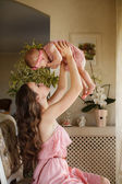 Portrait of happy young attractive mother playing with her baby girl near window in interior at haome. Pink dresses on mother and daughter — Stock Photo