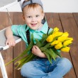 Smiling boy holding a bouquet of yellow tulips in hands sitting on wooden floor — Stock Photo