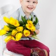 Portrait of Smiling boy with a bouquet of yellow tulips flowers in hands standing near white wall — Stock Photo