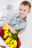 Portrait of Smiling boy with a bouquet of yellow tulips flowers in hands standing near white wall — Photo
